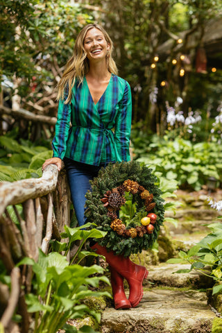 A woman with a Christmas wreath wearing the Marlena Plaid Wrap Top from Southern Tide.