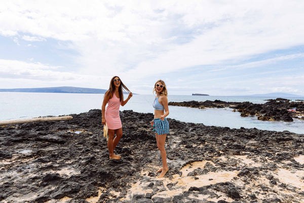 two girls walking on rocks on beach