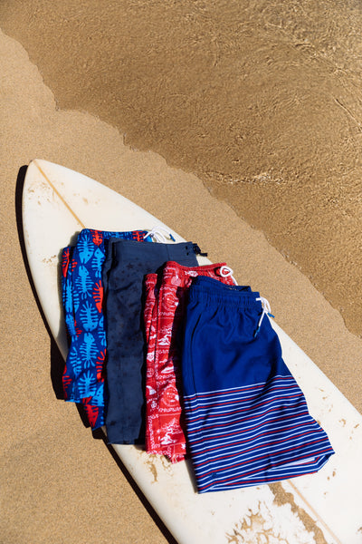 mens swim trunks on surfboard
