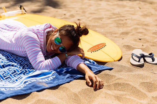 girl laying with surfboard on beach in sand