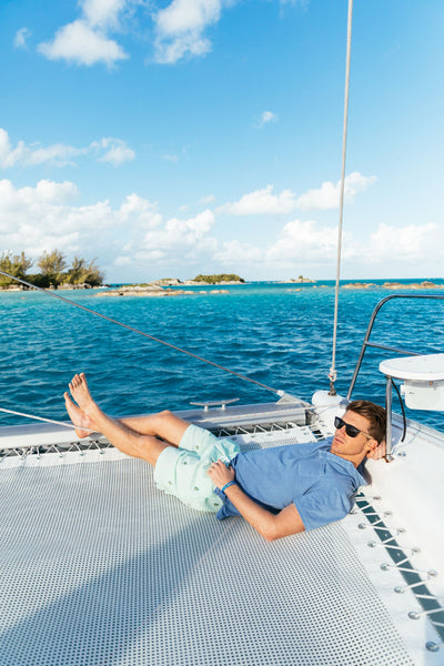 man relaxing on boat in islands