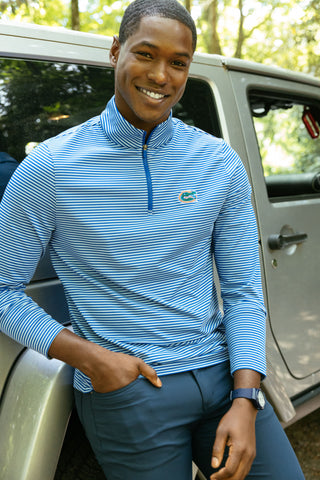 A man wearing Southern Tide's Collegiate Pullover and leaning against a car.