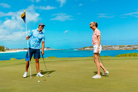 woman and man golfing at the beach