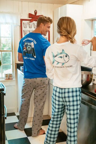 A man and a woman wearing Southern Tide graphic tees and lounge pants making breakfast together.