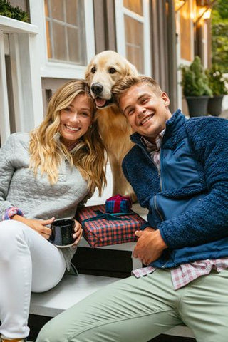 A man and a woman wearing Southern Tide warm layers and sitting outside with their dog.