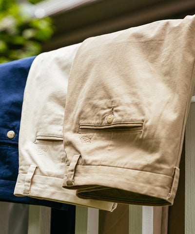 Southern Tide Navy, Khaki, and Tan Men's Pants folded over a porch railing.