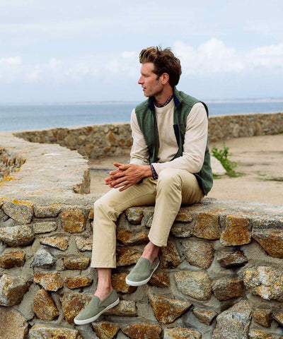 A man wearing Southern Tide Khaki Pants and a green vest on a beach.