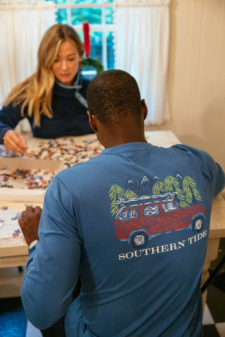 A man and woman in Southern Tide apparel working on a puzzle together.