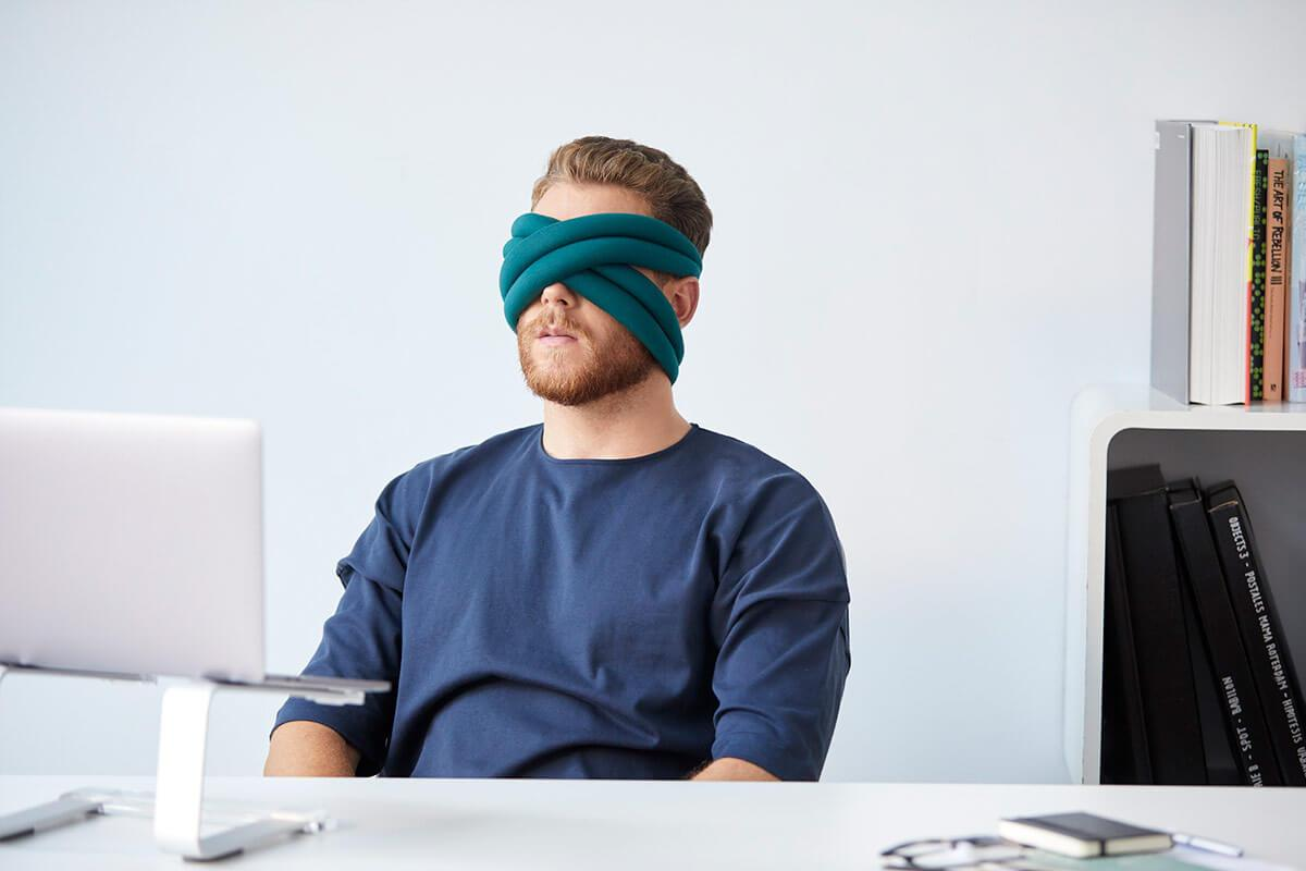 ostrichpillow_loop_eye-mask-pillow_office-desk_man_blue-reef