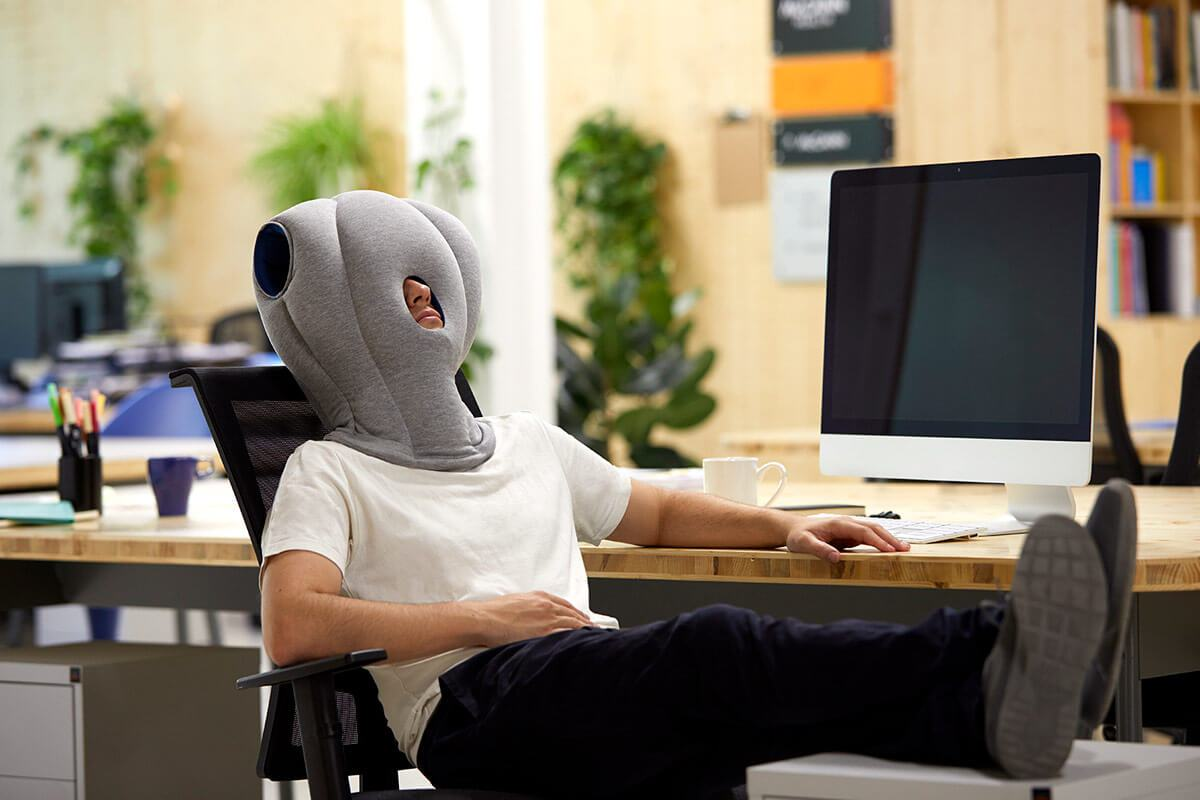 ostrichpillow_original_napping-desk-travel-pillow_office_man_sleepy-blue