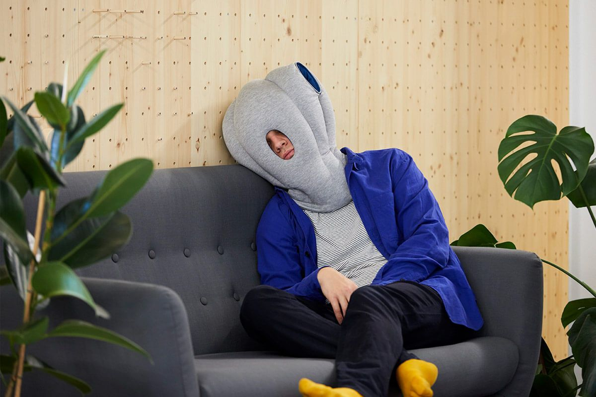 ostrichpillow_original_napping-desk-travel-pillow_home_man_sleepy-blue