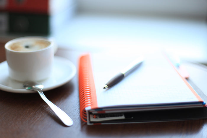 Coffee cup, pen and notepad on a table