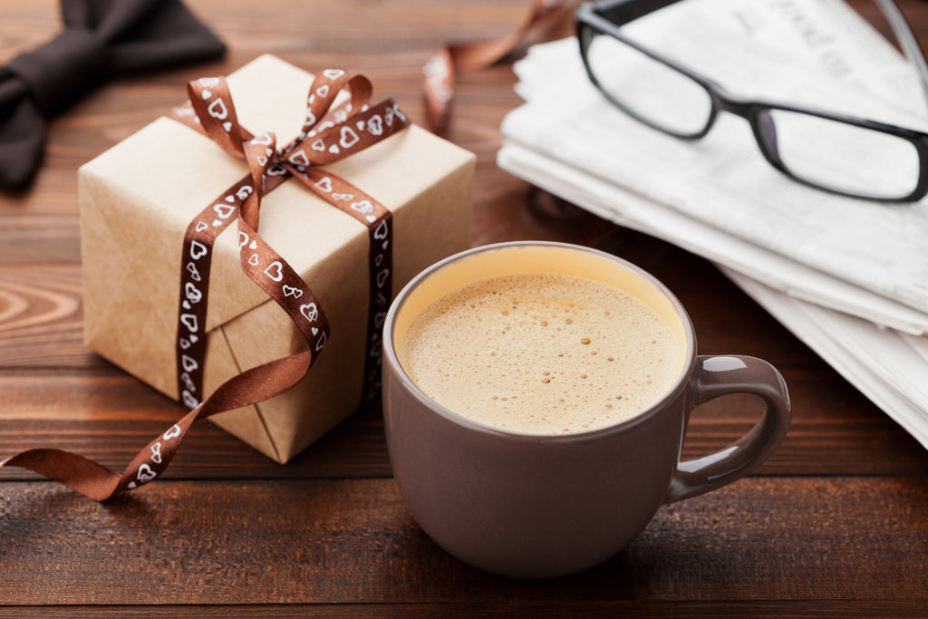 A wrapped gift next to a cup of coffee and glasses on a table