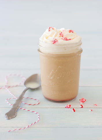 Peppermint White Chocolate Mocha in a glass with whipped cream and peppermint candy crumbles
