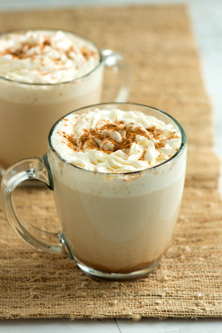 Two Pumpkin Spice Lattes in a glass with cream and cinnamon on top