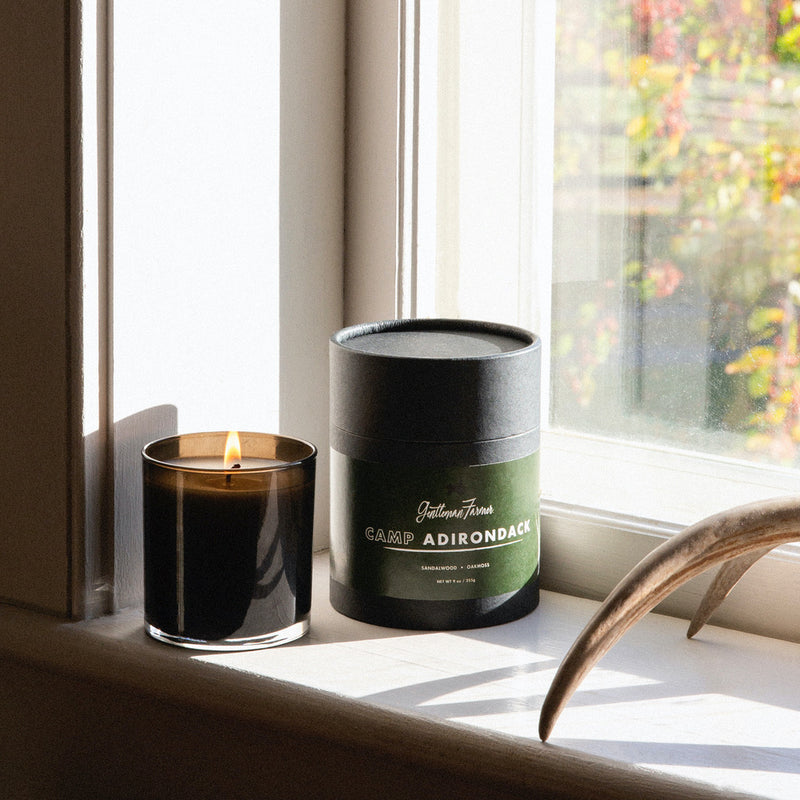 Lit candle in black glass vessel on a window still with packaging and antler, with a view of fall folliage outside.
