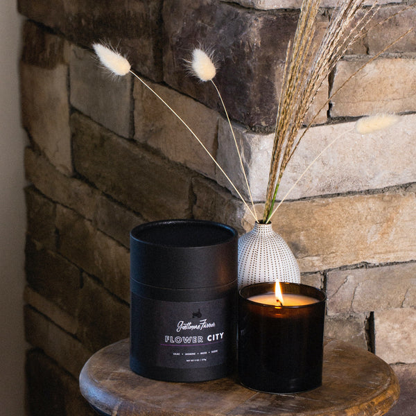 Lit candle in black glass vessel on side table with packaging and dried floral arrangement