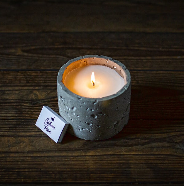 Lit candle in a grey cement vessel on a dark wood table