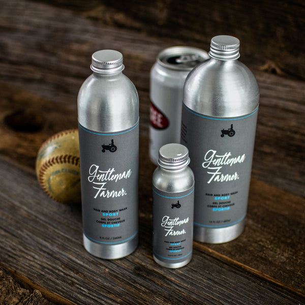 Three aluminum bottles of Hair and Body Wash Sport in different sizes, with grey labels, on a dark wood table, with an old baseball and a shower Genesee Beer
