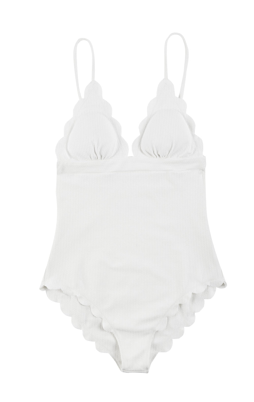 A white one piece swimsuit in a luxurious fabric, featuring a signature scallop trim