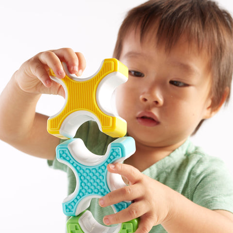 Grippies® Stackers - 24 Piece Set.  The stimulating blocks and cylinders encourage patterning, balancing, and matching skills with four bright colors and textures.
