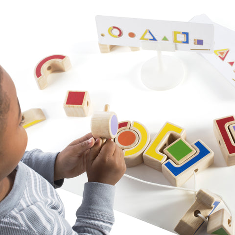 Nest and Lace Shapes.  Toddlers practice their hand-eye coordination, shape identification and patterning abilities.