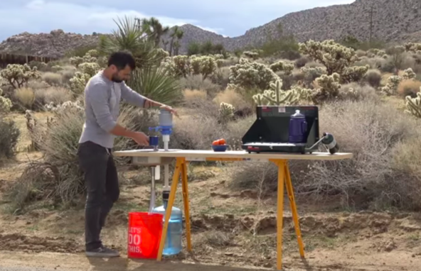 A man using a DIY camping sink.
