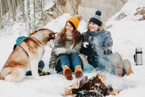 The happy couple with dog haski at the forest nature park in cold season.
