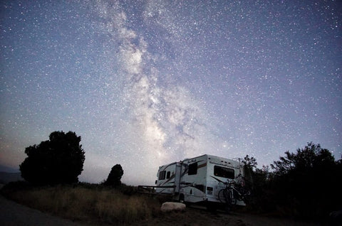 An RV beneath a starry sky.
