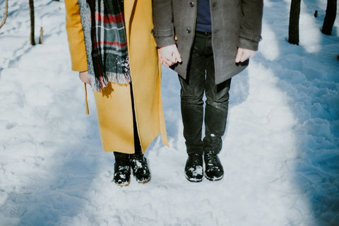 body shot of two people standing straight together and holding hands in winter