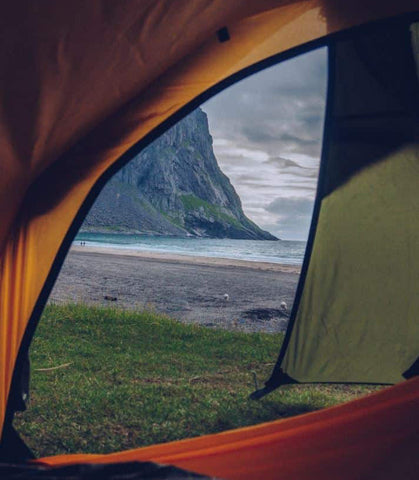A view of a beach as seen from a tent.