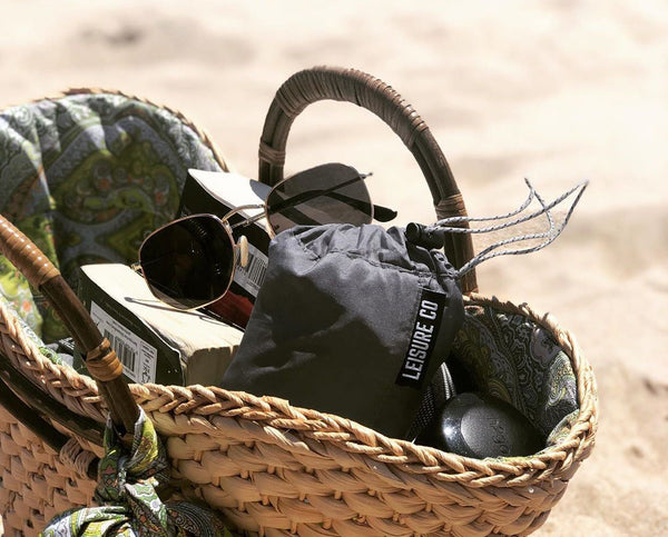 A beach bag packed with a Leisure Co camping pillow.