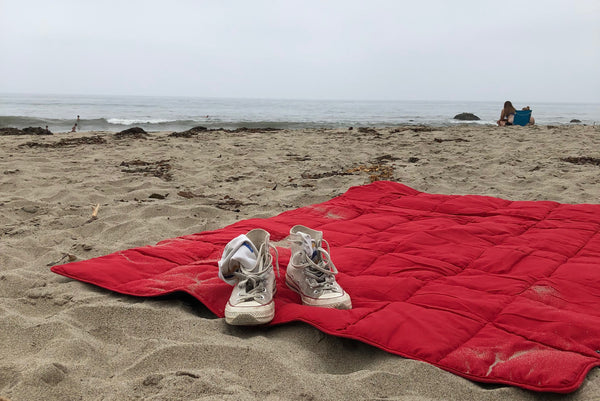A pair of shoes on a Leisure Co Blanket on the beach.