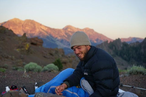 A man in a camp site wearing a down insulated jacket