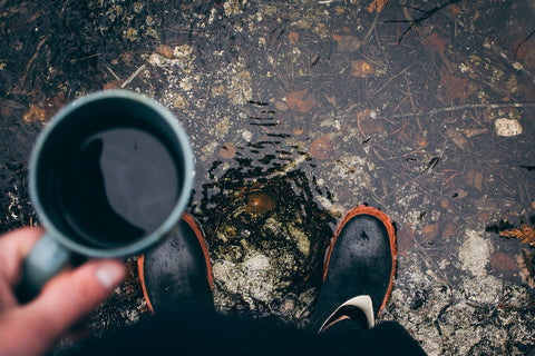 holding cup in puddle with rain boots
