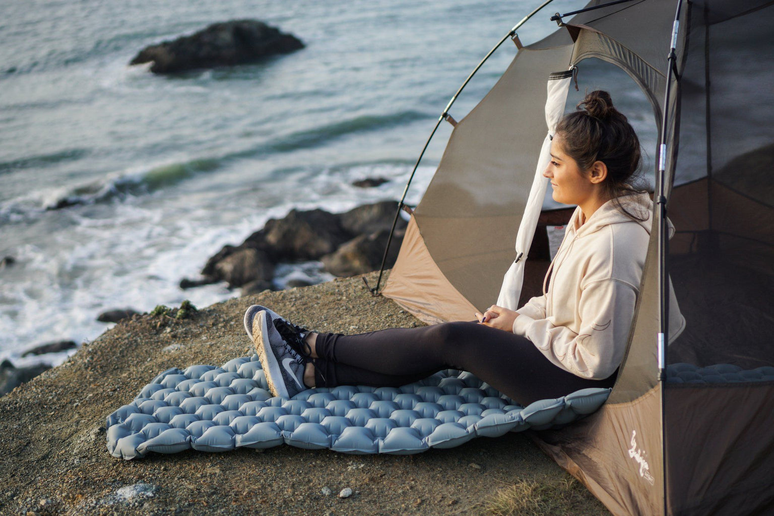 A woman sitting on a sleeping pad.