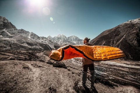 A guy carrying a yellow sleeping bag in a campsite