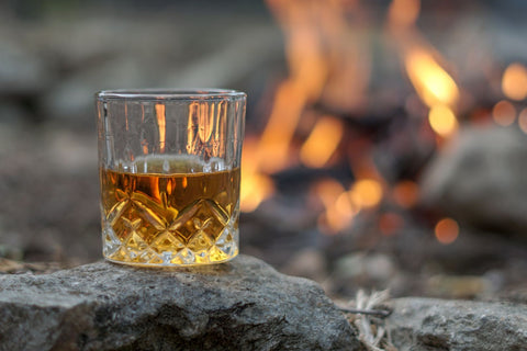 glass of whiskey by a camp fire