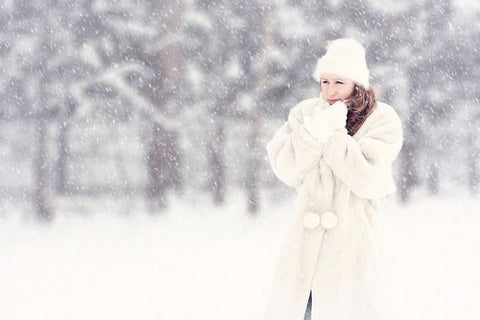 a lady in white winter clothing during winter