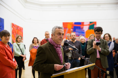 Stewart Geddes speaks into a microphone at the RWA, people stand behind him, with bright abstract paintings on the wall in the background