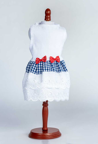 An adorable, one-of-a-kind white top with gingham and eyelet skirt and bow trim for your dog.