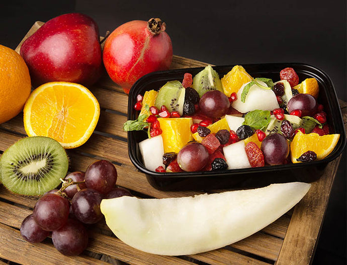 exotic fruit salad with kiwi, blueberry, cranberry, egyptian orange, washington apple, red grapes, pineapple, honeydew melon, strawberry, mint leafs, and honey lemon seasoning