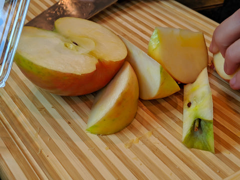 Apples being sliced on a cutting board