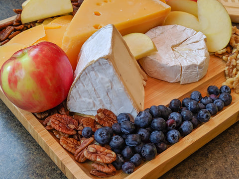 Cheese board with berries, nuts, and fruits