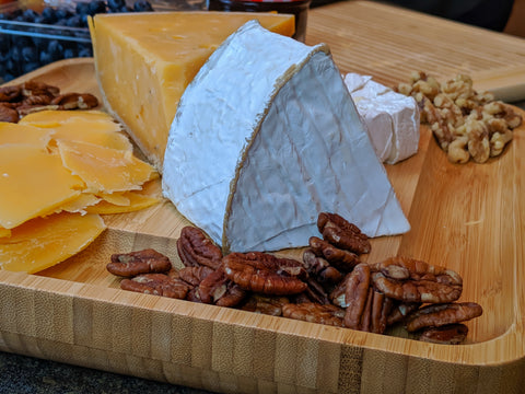 Nuts and cheeses on bamboo cheese board from Vistal