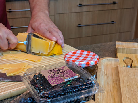 Cutting gouda for cheese board with fruits and jam in foreground
