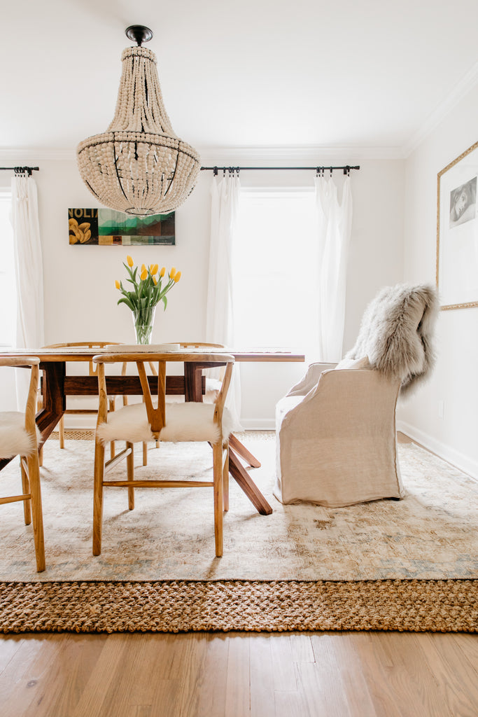 Mismatched dining chairs, vintage turkish persian rug layered over jute, and cloudlike linen curtains.