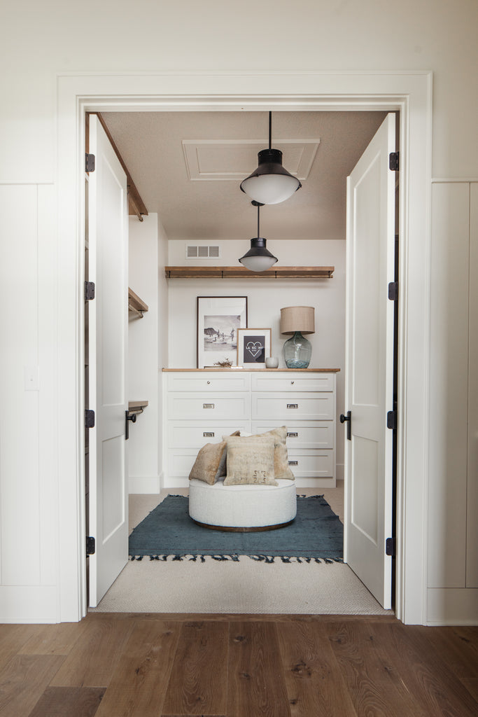Master closet design with built in cabinetry and boutique style clothes rack.