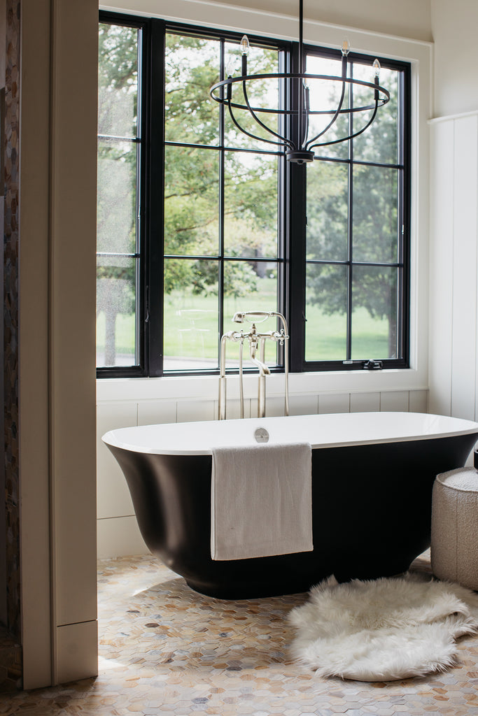 Master bath with black bathtub, black windows, and marble floor.