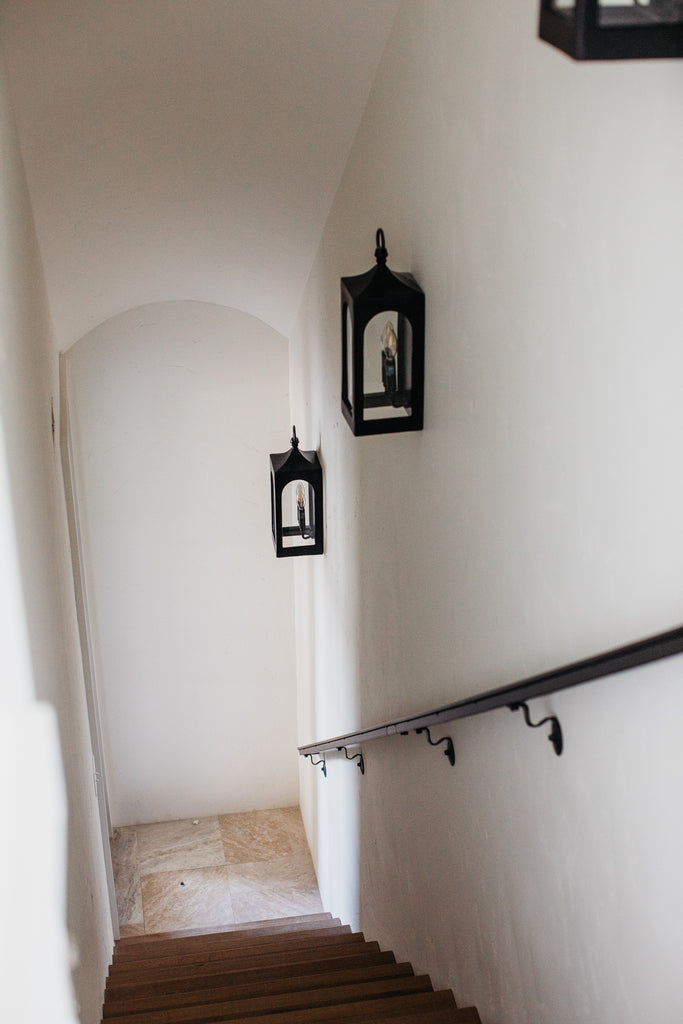 Secret staircase with sconces and barrel ceiling detail.